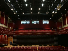 A red seating area for an auditorium with stage facility panel