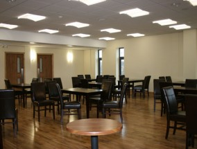 Inside a function room with wooden flooring, leather seats and brown tables