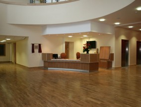 A large reception area with wooden floors and wooden desk